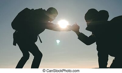 teamwork tourists business travel trip lends a helping hand. two men with backpacks hiking help each other silhouette in mountains with sunlight. slow motion video. teamwork friendship hiking help each other trust assistance the silhouette in mountains, sunrise lifestyle . victory is the way to success