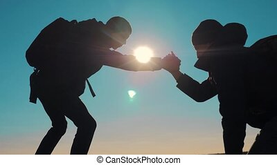 teamwork tourists business travel trip lends a helping hand. two men with backpacks hiking help each other silhouette in mountains with sunlight. slow motion video. teamwork friendship hiking help each other trust assistance the silhouette in mountains, sunrise . lifestyle victory is the way to success