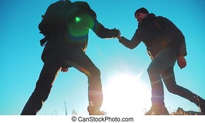 teamwork tourists business travel trip lends a helping hand. two men with backpacks hiking help each other silhouette in lifestyle mountains with sunlight. slow motion video. teamwork friendship hiking help each other trust assistance the silhouette in mountains, sunrise. victory is the way to success