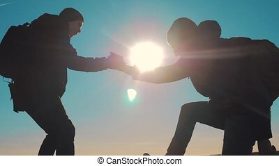 teamwork tourists business travel trip lends a helping hand. two men with backpacks hiking help each other silhouette in mountains with sunlight. slow motion video. teamwork friendship hiking help each other trust assistance the silhouette in mountains lifestyle , sunrise. victory is the way to success