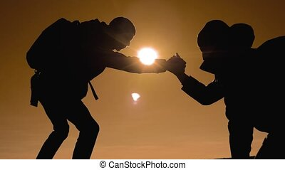 teamwork tourists business travel trip lends a helping hand. two men with backpacks hiking help each other silhouette in mountains with sunlight. slow motion video. teamwork friendship hiking help each other trust assistance the silhouette in mountains, lifestyle sunrise. victory is the way to success