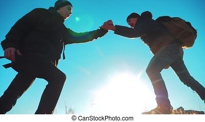 teamwork tourists business travel trip lends a helping hand. two men with backpacks hiking help each other silhouette lifestyle in mountains with sunlight. slow motion video. teamwork friendship hiking help each other trust assistance the silhouette in mountains, sunrise. victory is the way to success