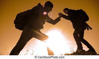 teamwork tourists business travel trip lends a helping hand. two men with backpacks hiking help each other silhouette in mountains lifestyle with sunlight. slow motion video. teamwork friendship hiking help each other trust assistance the silhouette in mountains, sunrise. victory is the way to success