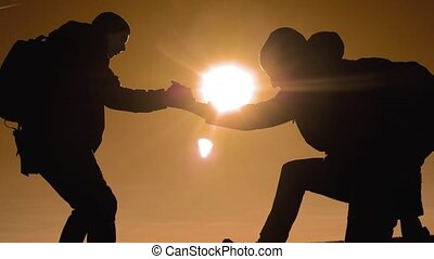teamwork tourists business travel trip lends a helping hand. two men with backpacks hiking help each other silhouette in mountains with sunlight. slow motion video. teamwork friendship hiking help each other trust assistance the silhouette lifestyle in mountains, sunrise. victory is the way to success
