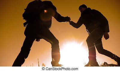 teamwork tourists business travel trip lends a helping hand. two men with lifestyle backpacks hiking help each other silhouette in mountains with sunlight. slow motion video. teamwork friendship hiking help each other trust assistance the silhouette in mountains, sunrise. victory is the way to success
