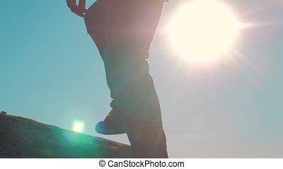 teamwork tourists business travel trip. two men with backpacks hiking help each other silhouette in mountains with sunlight. slow motion video. teamwork friendship hiking help each other trust assistance the silhouette in mountains, sunrise . victory is the way to success lifestyle