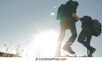 teamwork tourists lifestyle business travel trip lends a helping hand. two men with backpacks hiking help each other silhouette in mountains with sunlight. slow motion video. teamwork friendship hiking help each other trust assistance the silhouette in mountains, sunrise. victory is the way to success