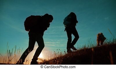 teamwork. Two hikers enjoying sunrise walking from top of a mountain and dog. slow motion video. Two hikers with backpacks climbing a peak on cloud sky background and dog. hikers adventure and the dog go walking. travel victory is the way to success silhouette lifestyle concept