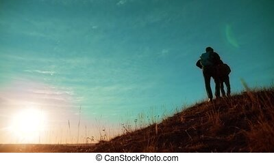 teamwork. Two hikers enjoying sunrise walking from top of a mountain and dog. slow motion video. Two hikers lifestyle with backpacks climbing a peak on cloud sky background and dog. hikers adventure and the dog go walking . travel victory is the way to success silhouette concept