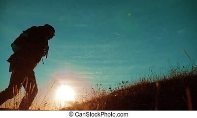 teamwork. Two hikers enjoying sunrise walking from top of a mountain and dog. slow motion video. Two hikers with backpacks climbing a peak on cloud sky background and dog. hikers adventure and the dog go walking. travel victory is the way to success silhouette concept lifestyle