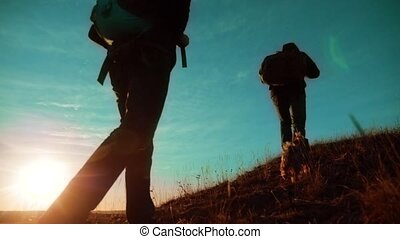 teamwork. Two hikers enjoying sunrise walking from top of a mountain and dog. slow motion video. Two hikers with backpacks lifestyle climbing a peak on cloud sky background and dog. hikers adventure and the dog go walking . travel victory is the way to success silhouette concept