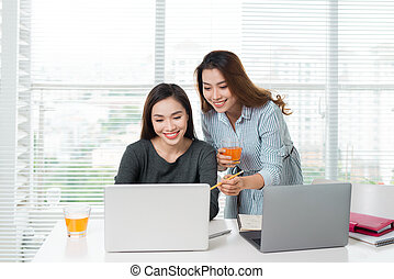 Teamwork. Two smiling young business women sitting in office at table and working