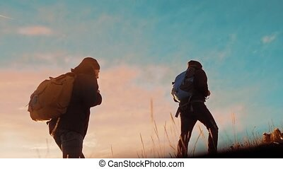 teamwork. two tourists hikers men with backpacks at sunset go hiking trip. hikers adventure and the dog go walking. travel lifestyle mountains silhouette