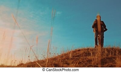 teamwork. two tourists hikers men with backpacks at sunset go hiking trip. hikers adventure and the dog lifestyle go walking. travel mountains silhouette