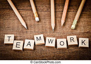 TEAMWORK word written on wood block with wood pencils.