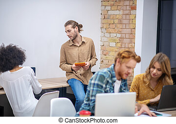Team of young professionals working in the office together and looking involved