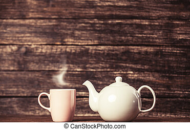 Teapot and cup of tea on wooden table.