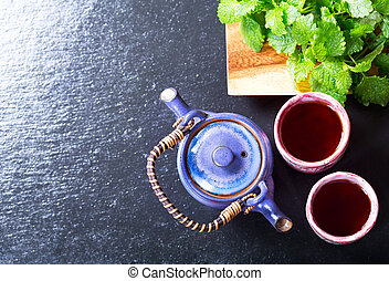 Teapot and cups of tea with mint on dark background,