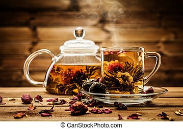 Teapot and glass cup with blooming tea flower inside against...