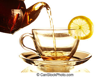 Teapot and Teacup - Teapot and glass cup of tea with lemon...