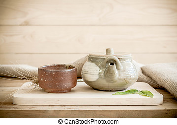 Teapot on wooden and sackcloth background.