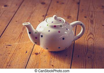 Teapot on wooden floor