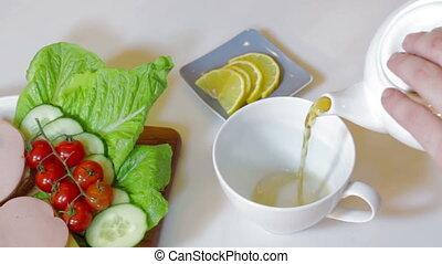 Teapot pouring tea into cup