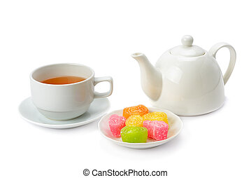 Teapot, tea in a cup and jujube isolated on white background.