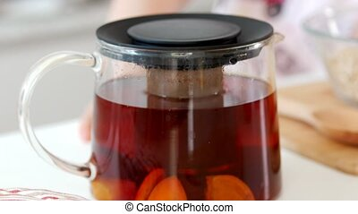 Teapot with fruit tea and ingredients for cooking on the...