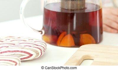 Teapot with fruit tea in front of hands of girl preparing...