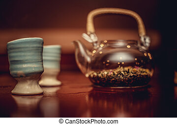 Teapot with herbs and cups.