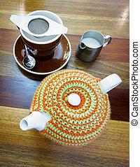 Teapot with tea cozy, tea cup and a jug of milk