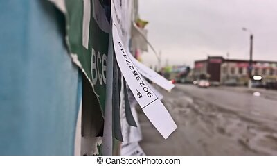 Tear off paper wall paper ads notice on the wall road going...