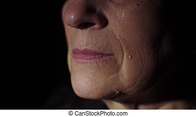 Tears on a woman's face - Aged woman crying at dark room