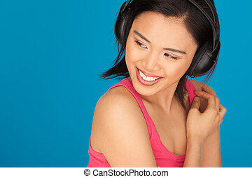 Teasing beautiful Asian woman looking back over her shoulder with a lovely smile on a blue background with copyspace