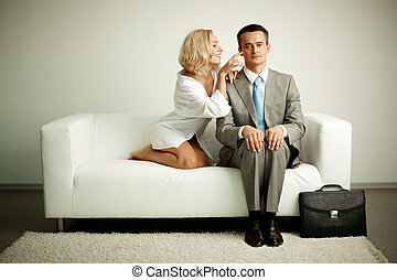 Teasing - Photo of serious man sitting on sofa with...