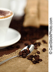 teaspoon of coffee with beans on jute
