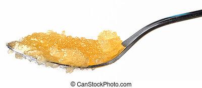 Teaspoon of honey isolated on white background.