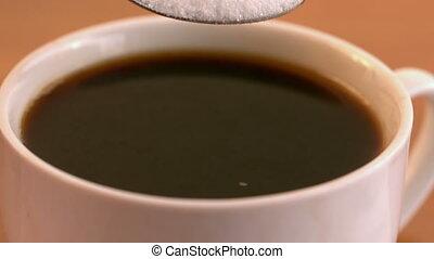 Teaspoon of sugar plunging into coffee cup