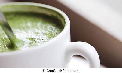 teaspoon stirring matcha green tea latte in cup - drink,...