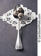 Teaspoon with quail eggs on white napkin