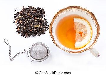 teatime - cup of tea with lemon, chai tea grains and infuser