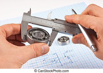 Technical drawing and callipers with bearing in hand