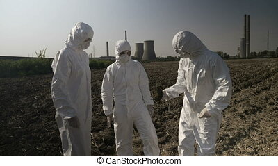 Technical team of lab employees in hazmat suits sampling and examining vegetation and soil from field near of power plant