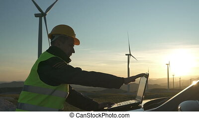 Technician Engineer in Wind Turbine Power Generator Station checks the status of the turbines using a laptop, sunset
