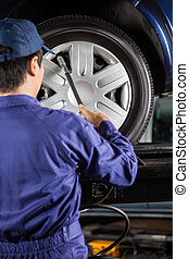 Technician Filling Air Into Car Tire At Garage