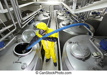 technician filling large tank - fully protected in yellow ...