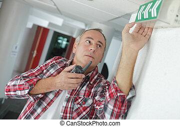 technician fitting an emergency sign