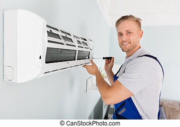 Technician Fixing Air Conditioner - Young Male Technician...