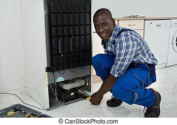 Technician Fixing Refrigerator